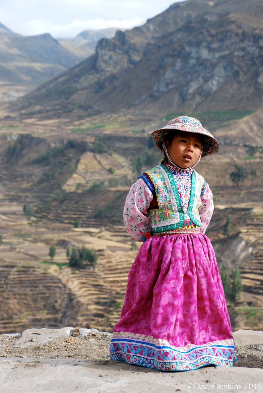 Little girl posing for photos with her grandma and lama en route to Colca Canyon, Peru.