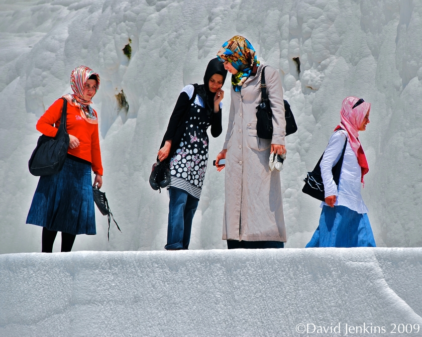 The colourful garments make for an interesting contrast against the travertine terraces at Pamukkale, Turkey.
