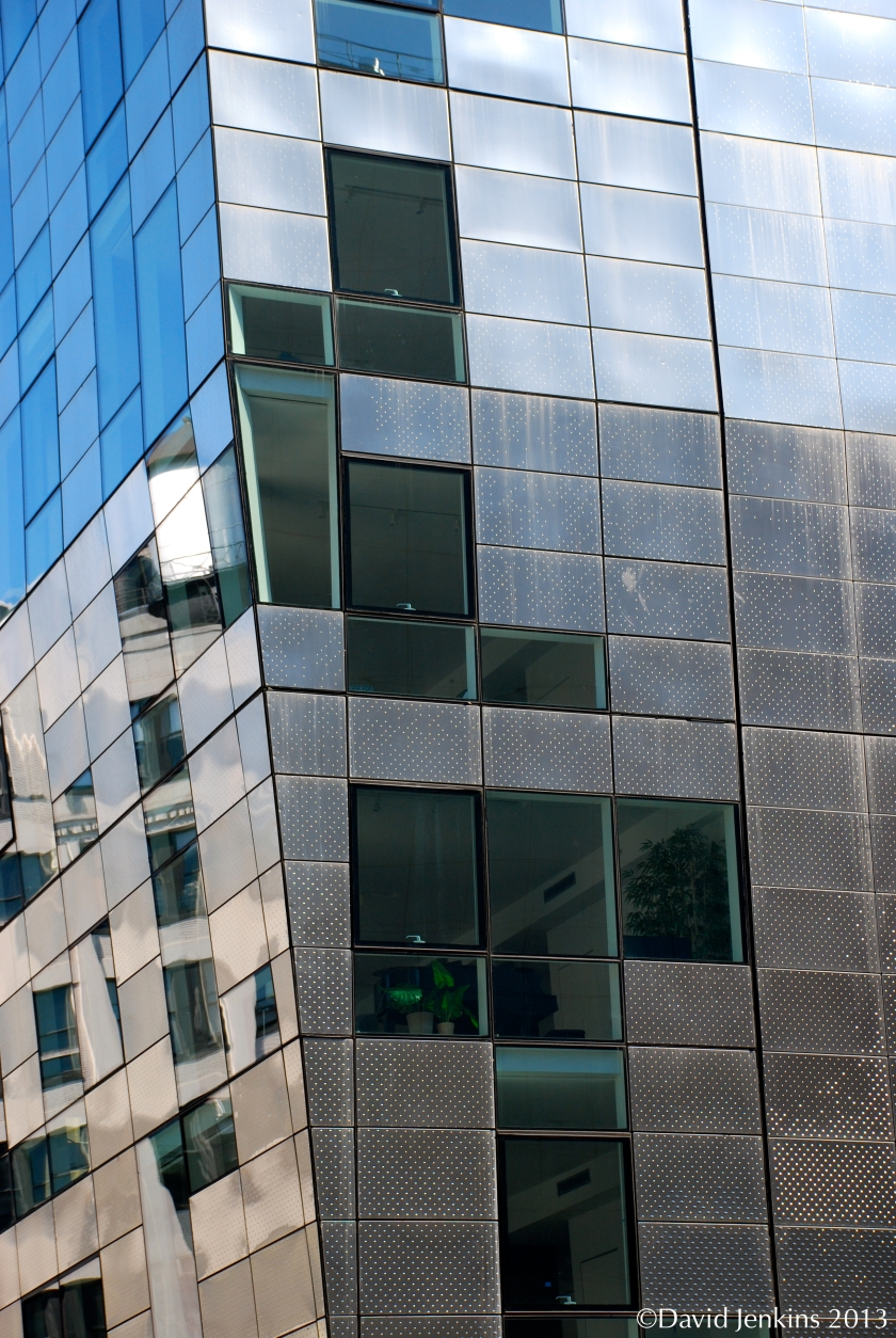 245 Tenth Avenue on the High Line in New York City has a singular façade of glass with stainless steel panels.